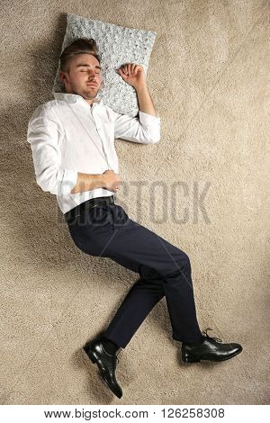 Young businessman sleeping on the floor