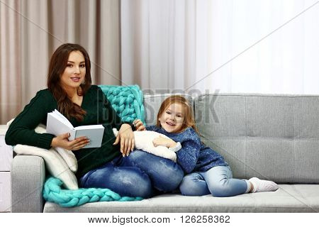 Happy pregnant woman reading book for her child on couch