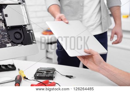 Young repairer getting broken laptop in service center