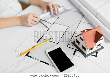 business, architecture, building, construction and people concept - close up of smartphone and living house layout over architect hands with compass measuring blueprint