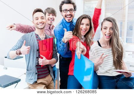 Group of students celebrating success in exams being cheerful throwing arms up