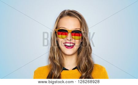 people, patriotism and nationality  concept - happy young woman or teen girl face in sunglasses with german flags over blue background