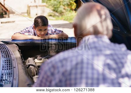 Family and Generation gap. Old grandpa spending time with his grandson. The senior man shows the engine of a vintage car from the 60s to the preteen child. They boy smiles happy.