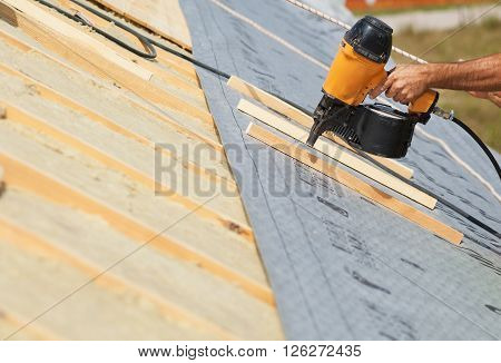 Building contractor worker (roofer) with a air nail gun nailer working on the roof on a new home constructiion project