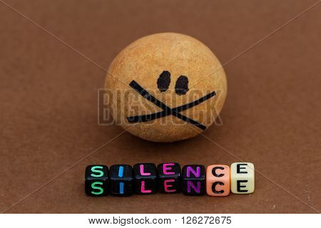 Brown round ball with eyes and X symbol representing silent. Concept of keeping silent,abuse,secret,torture,harassment,violence.