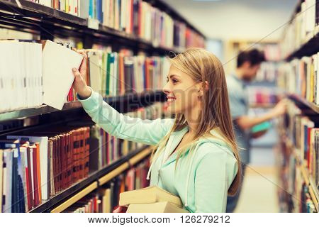 people, knowledge, education and school concept - happy student girl or young woman taking book from shelf in library