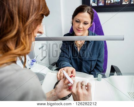Cropped Image Of Manicurist Performing Manicure On Customer's Ha