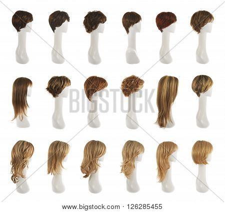 Hair wig over the white plastic mannequin head isolated over the white background, set of multiple different wigs in the side foreshortening