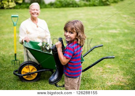 Smiling boy holding wellington boots besides granny in yard