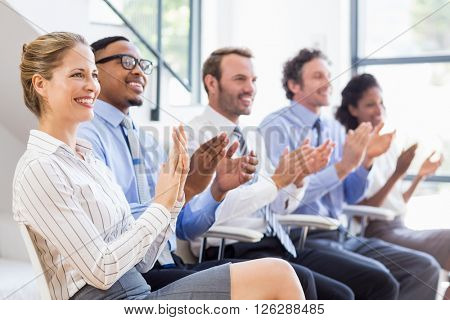 Businesspeople applauding while in a meeting at office