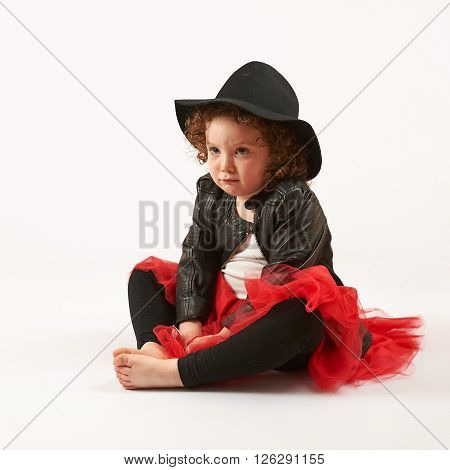 Little girl with black hat sitting and pouting