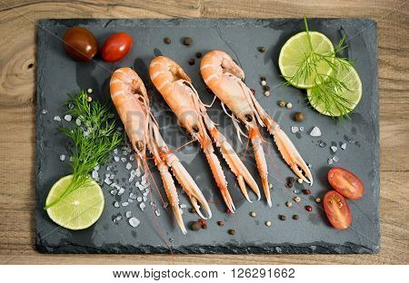 Scampi, lemon lime, white salt and cherry tomatos on the black rock.