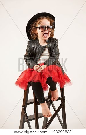 Little girl with black hat and sunglass sitting on a high stool and dabbles
