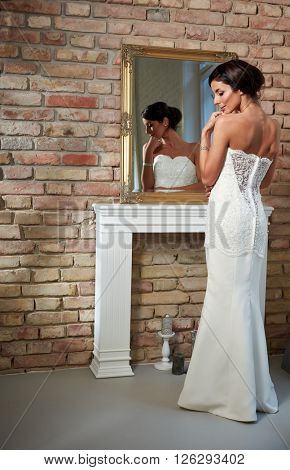 Beautiful bride standing front of mirror, photographed from behind. Full size.