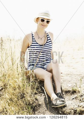 Young caucasian woman in a sailor outfit posing in outdoor. Tourism theme.