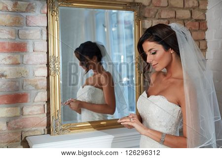 Beautiful young bride standing front of mirror, looking at engagement ring. Side view.