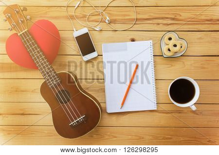 Blank Note Book And Pencil With Coffee,cookie, Mobile And Ukulele In Vintage Style On Jointed Wooden