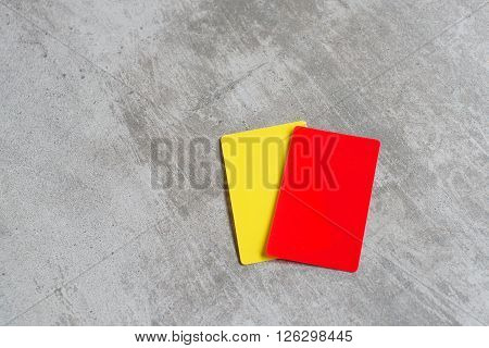 Referee red and yellow card used in football and soccer. Concrete background