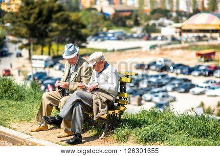 TIRANA, ALBANIA - CIRCA JUNE 2015: Elder men dressed well sit on the bench near Grand park in Tirana. Life during pension in Albania