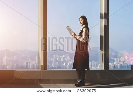 Young Asian businesswoman is using digital tablet for searching needed information for upcoming conference while is standing in office interior against big window with city view on background