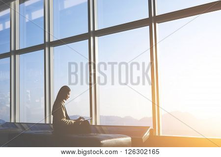 Silhouette of young asian woman is sitting in departure terminal of the airport building while is using digital tablet for connect to wireless.Asian female entrepreneur is sitting front office window