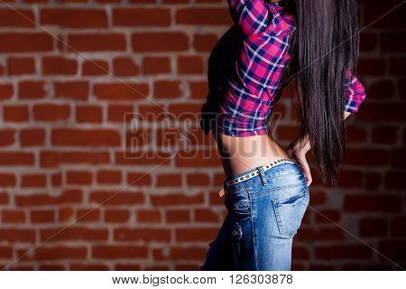 Sexy woman ass and back in jeans on red brick background. Girl with perfect torso bottom view