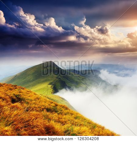 A great view of the foggy hills and cloudy sky which glowing by sunlight. Dramatic and picturesque morning scene. Location place: Carpathian, Ukraine, Europe. Artistic picture. Beauty world.