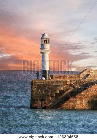 Lighthouse against sunset in Penzance Cornwall England UK