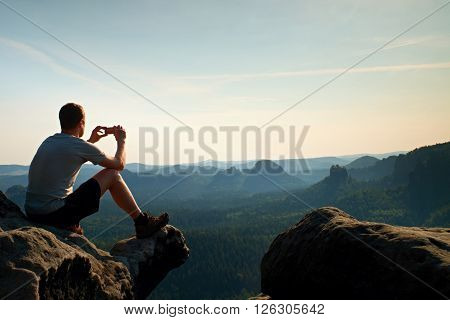 Tourist In Grey T-shirt Takes Photos With Smart Phone On Peak Of Rock. Dreamy Hilly Landscape Below,