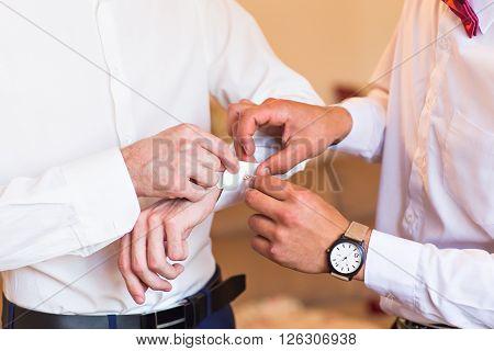 Groomsman helps to groom to put on cufflinks