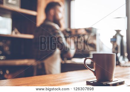 Morning coffee. Focused picture of coffee cup standing at bar counter with young bearded man in apron making coffee in background