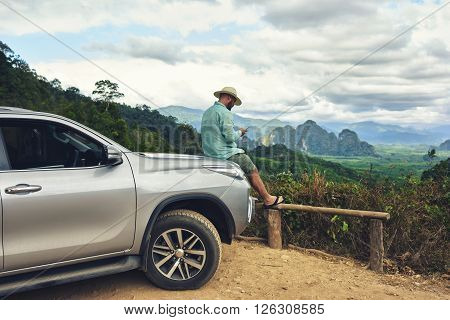 Young hipster guy is chatting on mobile phone while is sitting on automobile against beautiful jungle landscape.