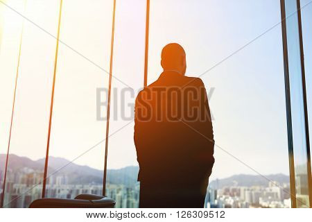 Silhouette of man managing director is examining the challenges the company after the refusal of investors in financing while standing in evening time against office window background with copy space