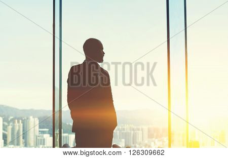 Silhouette of thoughtful businessman is thinking about future of his enterprise in times of great competition while is watching on view China outside the window.Copy space background for your content