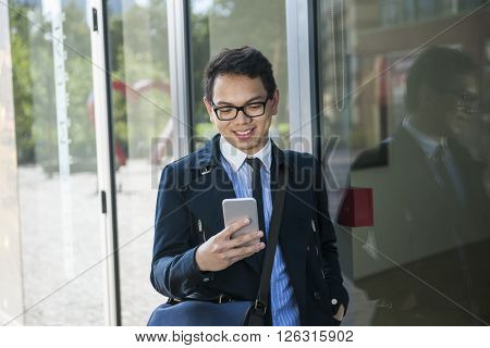 Young asian business man looking at mobile phone outside on city street near building poster