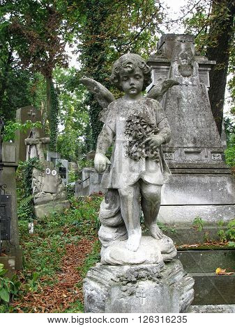 Ancient stone sculpture little girl-angel with wings she is holding a wreath of poppies and mourn for the dead
