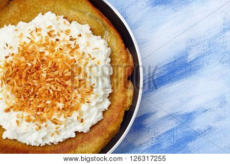 Pancake with cottage cheese and grated coconut kernel topping. Copy space overhead view.