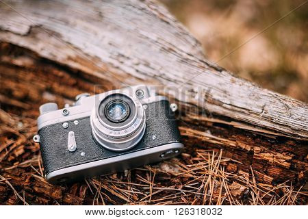 35mm Vintage Old Retro Small-Format Rangefinder Camera On Old Fallen Wood Tree In Forest. ** Note: Shallow depth of field