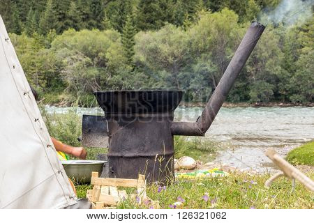 Expedition Campsite and Male Hand Adding Firewoods into Fumed Outdoor Kitchen Oven located on Grassy Meadow with Tent and Water Stream on Background