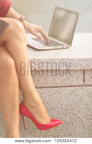 Close-up picture of businesswoman working outdoors and using laptop. Pretty lady with slim and slender legs sitting on concrete brick. Toned image.