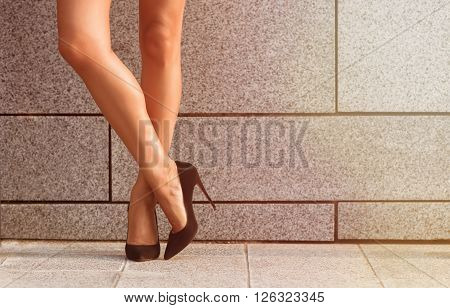 Beautiful slim and slender woman's legs isolated on black high heels. Crossed woman's legs isolated on brick wall background. Toned image.