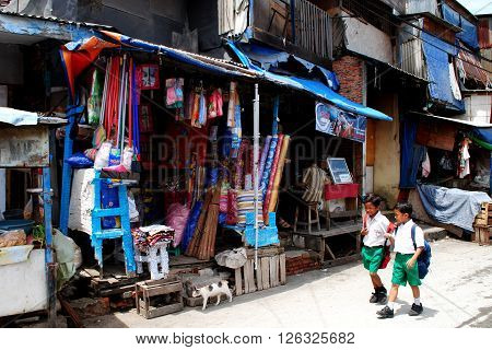 JAKARTA, INDONESIA, DECEMBER 15: Two boys in school uniform are walking past a shop in a street in Kota, the old town of Jakarta, on December 15, 2014.