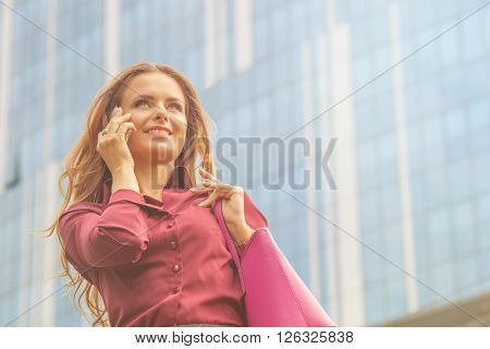 Businesswoman speaking over mobile phone and walking near office building. Pretty lady holding vivaceous bag at her hand in the city. Toned image.