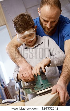 Closeup photo of diy father teaching son tinkering, using jig saw.