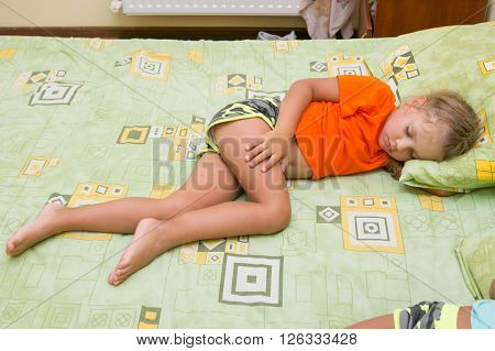 Little Girl Is Sleeping On His Side On The Big Bed Without A Blanket
