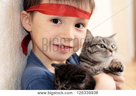 Boy holding stripped cat and black kitten