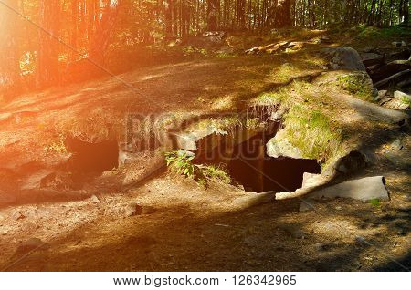 Summer sunny landscape - entrance to megalith on the territory of Vera Island in Southern Urals Russia. It is the part of greatest megalithic complex of the Ural Mountains. Soft focus processing