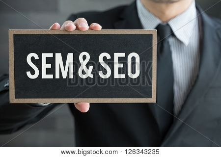 SEM and SEO message on blackboard and hold by businessman business concept