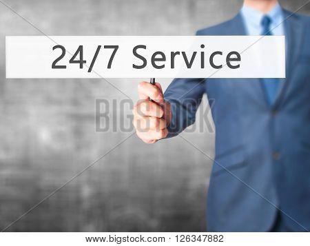 24/7 Service - Businessman Hand Holding Sign