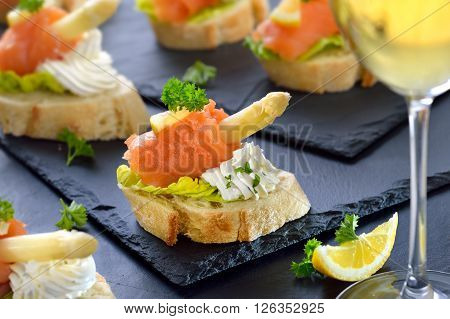 Delicious canapes with German white asparagus, cream cheese with herbs, smoked salmon on Italian ciabatta bread with lettuce leaves, served on slate boards, in the foreground a glass of white wine